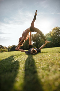 Couple doing acrobatic yoga on grass
