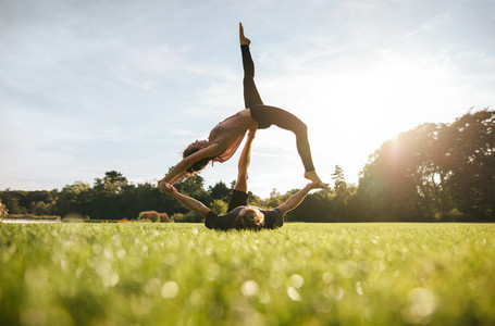 Young couple doing acrobatic yoga on lawn