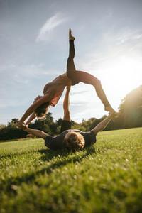 Couple doing acro yoga on grass