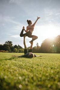 Healthy young couple doing acrobatic yoga