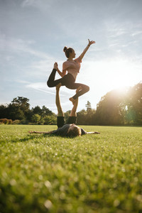 Healthy young couple doing acrobatic yoga