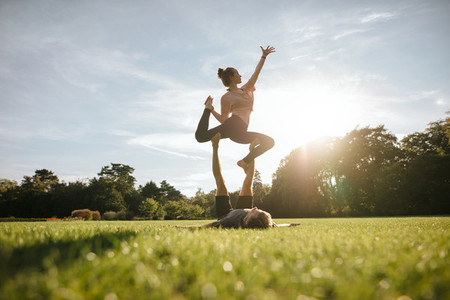 Healthy couple doing acro yoga on grass