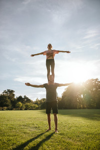 Couple doing acrobatic yoga exercise in park