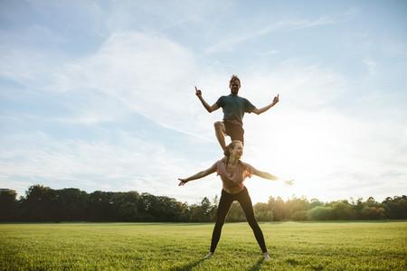 Strong young couple doing acrobatic yoga