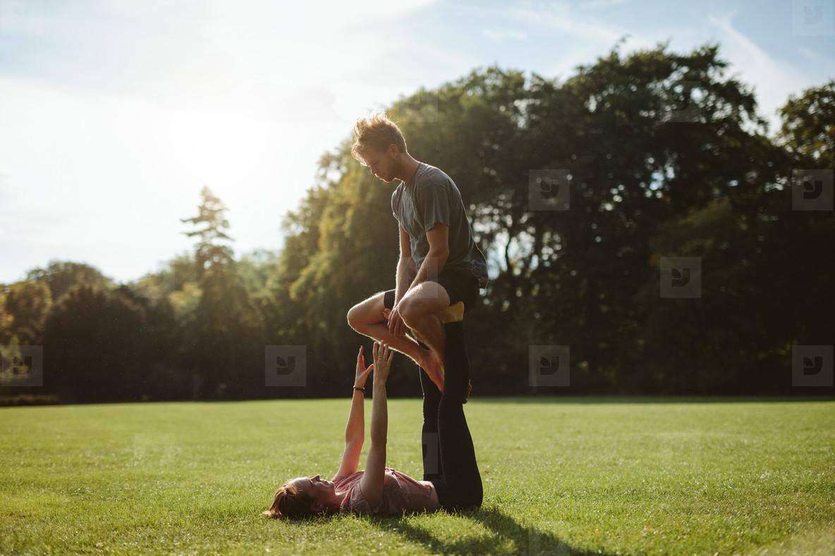 Couple in park practising pair acro yoga