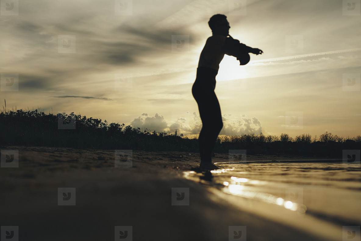 Silhouette of a male diver wearing wetsuit on beach