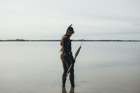 Spear fisherman in sea water with speargun