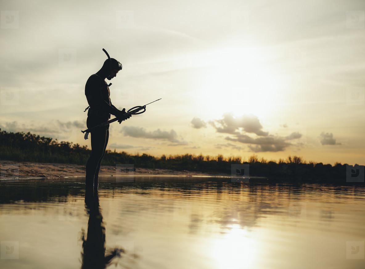 Spear fisherman checking speargun