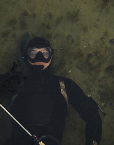 Spearfishing diver showing thumbs sign while in water