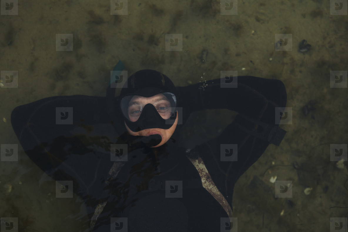 Relaxed man snorkeling in shallow water