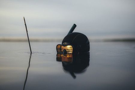 Spearfishing diver with reflection of sunset in diving mask