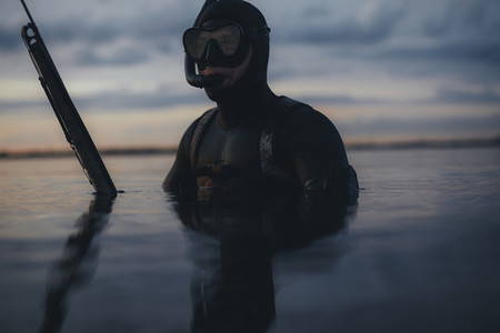 Spearfishing diver in a lake at evening