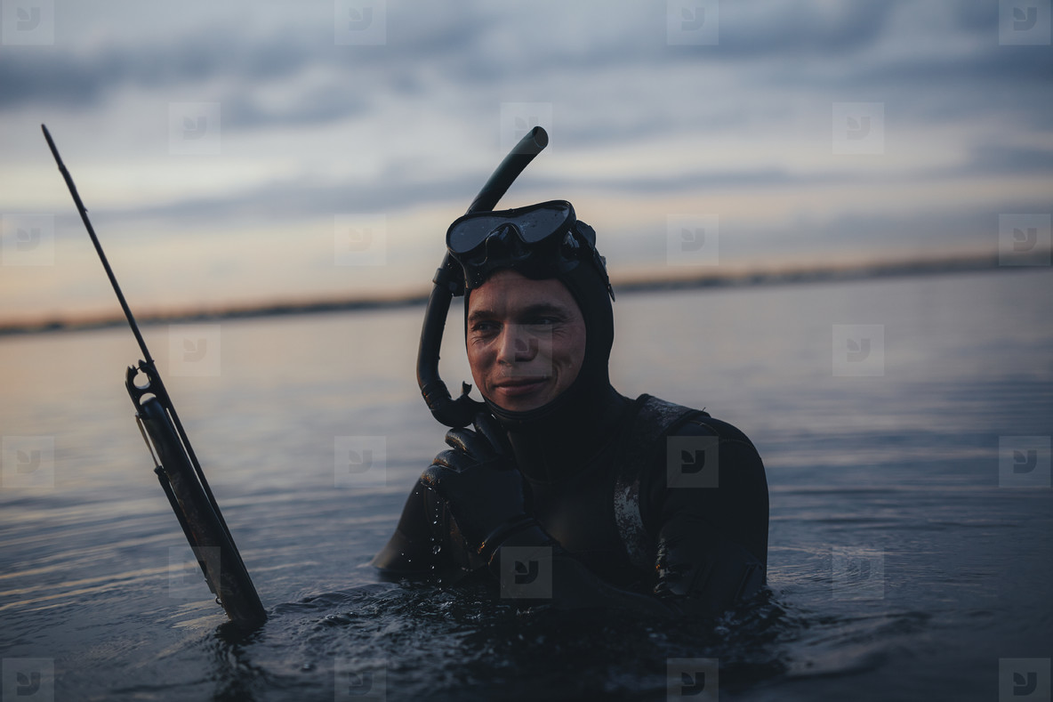 Happy underwater hunter with speargun