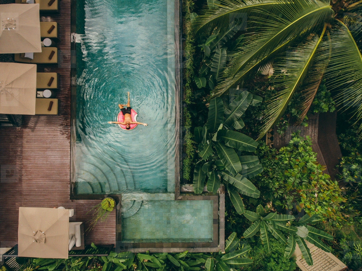 Luxury resort with man on inflatable ring in pool