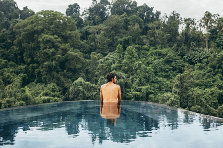 Young man standing in a infinity pool at resort