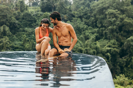 Young couple relaxing on the edge of pool