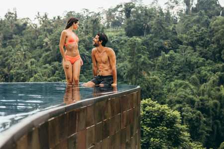 Loving young man and woman relaxing in pool