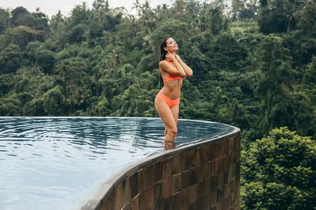 Young woman wearing bikini standing in swimming pool