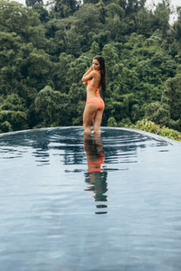 Sensual young woman standing in the pool