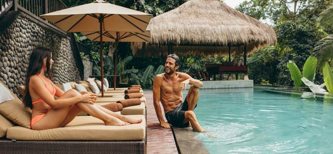 Couple relaxing at poolside of luxury resort