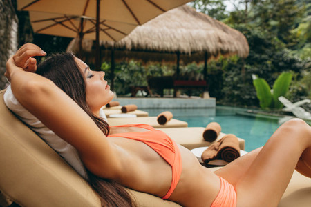 Woman in bikini relaxing on lounge chair at poolside