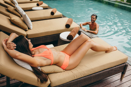Man in pool with woman on deckchair at poolside