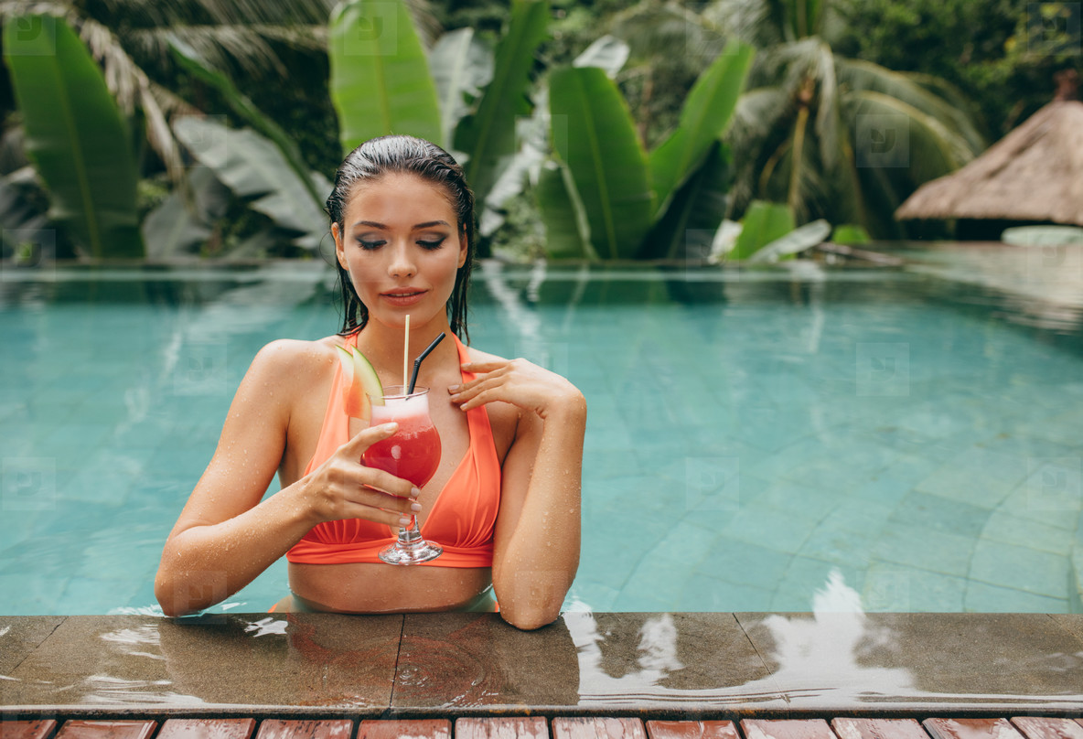 Young woman relaxing in pool and having cocktail