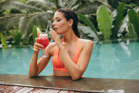 Young woman drinking cocktail in swimming pool