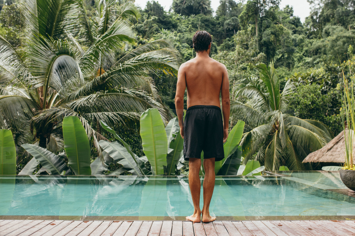Young man standing on the edge of the pool