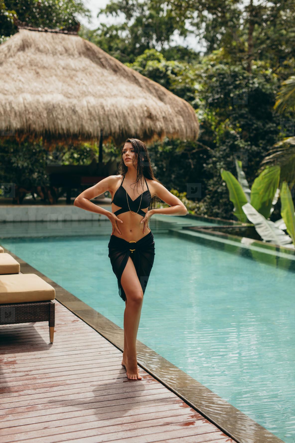 Attractive bikini model posing at poolside