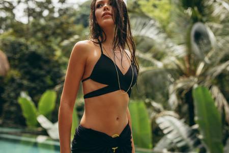 Young woman in black bikini looking away