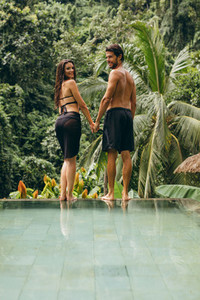 Love couple standing on the edge of the pool