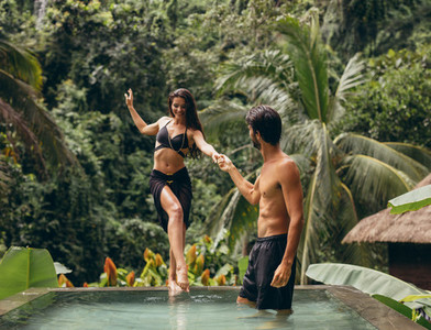 Man helping girlfriend entering the pool at resort