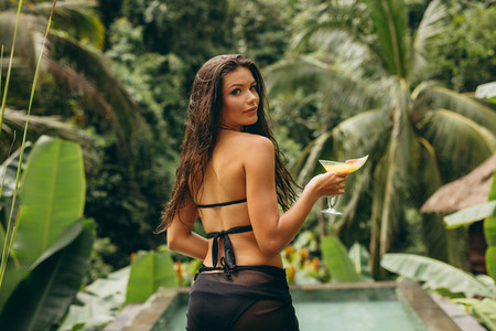 Beautiful young woman with cocktail at poolside