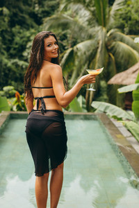 Sensual young woman with cocktail at poolside