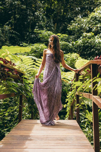 Attractive woman in a dress walking on small bridge