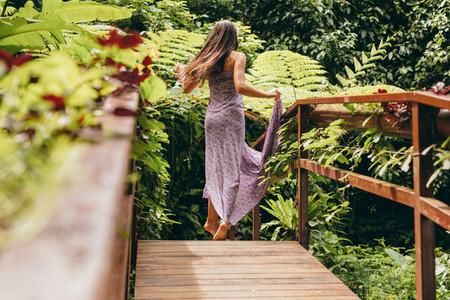 Woman in beautiful dress walking on wooden bridge in nature