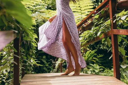 Female in dress walking on wooden bridge in nature
