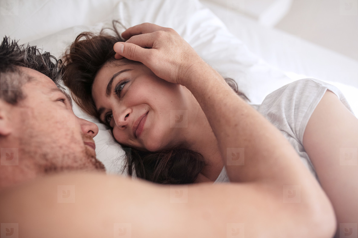 Romantic couple lying together on bed. Photos   Romantic couple lying together on bed   YouWorkForThem