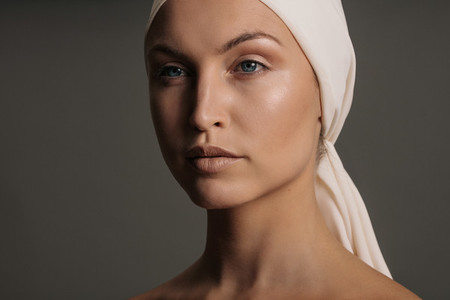 Young woman with head scarf looking away