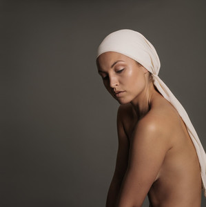 Young woman with naked body and head scarf