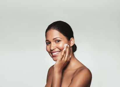 Smiling woman applying moisturizer on her face