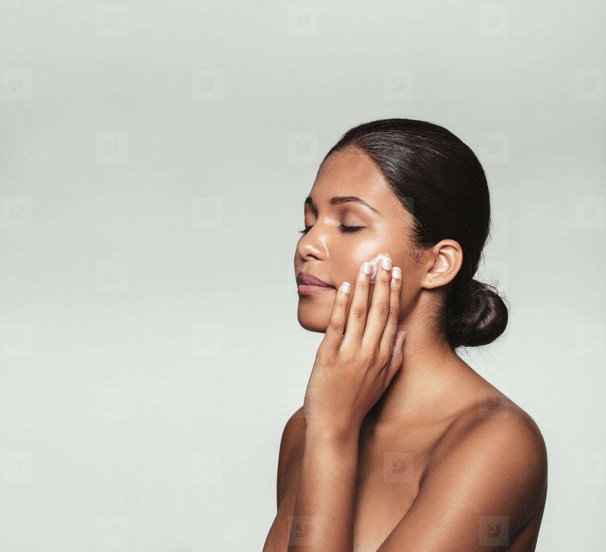 Beautiful young woman applying moisturizer to her face