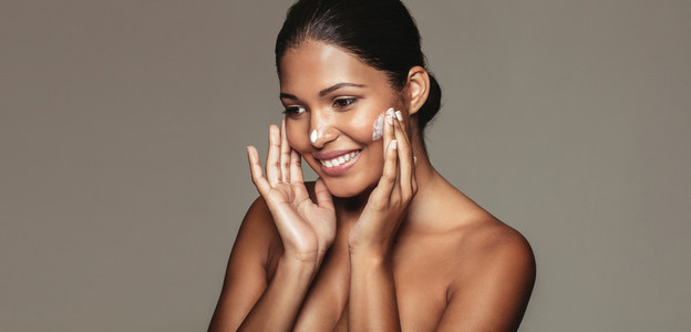 Beautiful woman applying cosmetic cream to her face