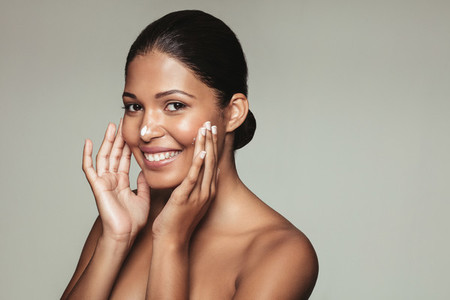 Smiling female model applying moisturizer