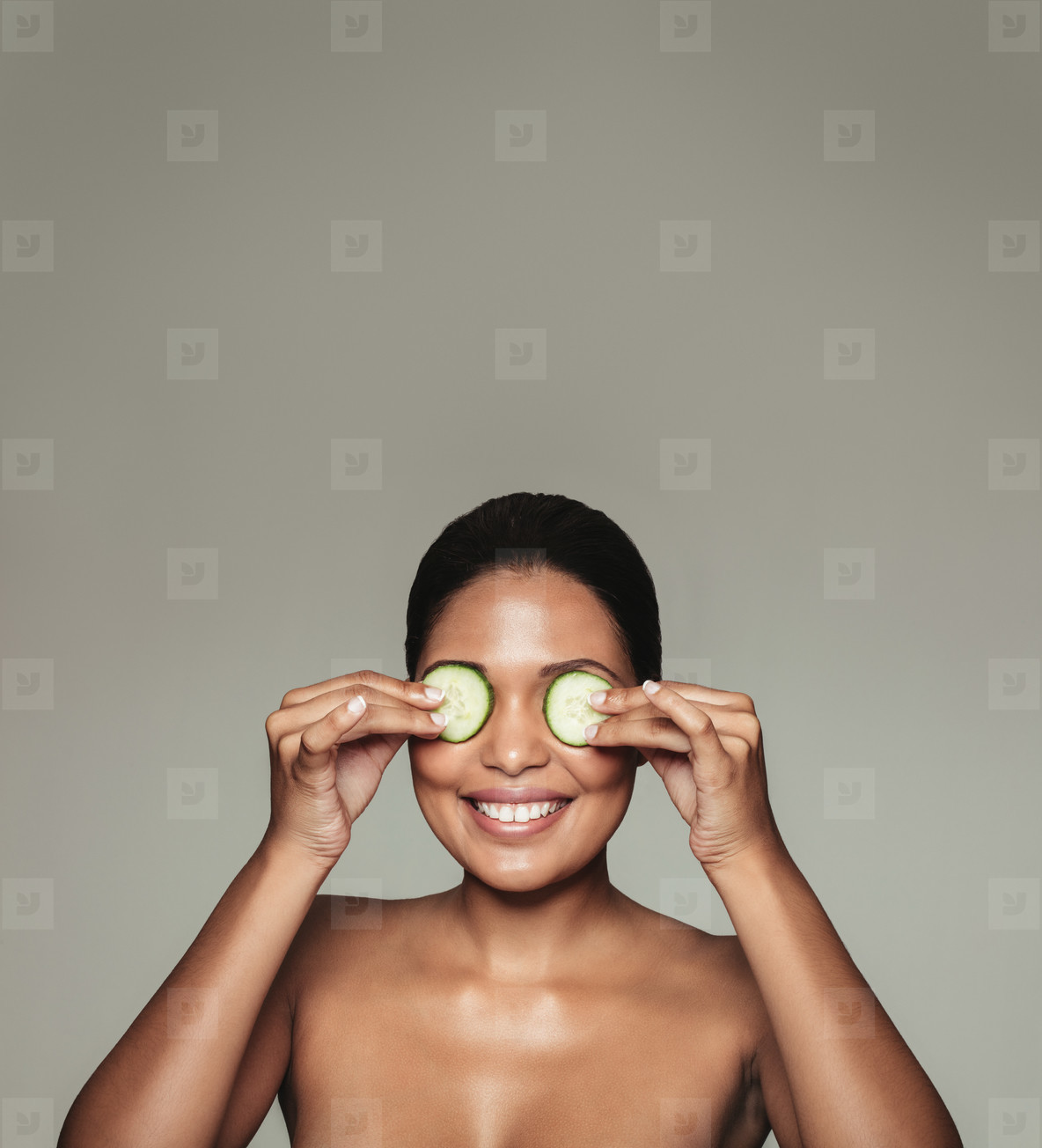 Woman holding cucumber over eyes