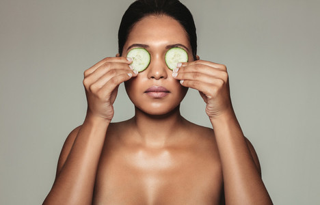 Beautiful woman holding cucumber over eyes