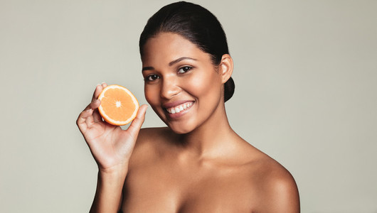 Beautiful young woman holding an orange