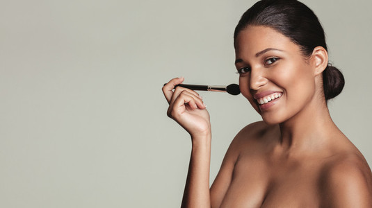 Smiling young woman applying make up with a brush