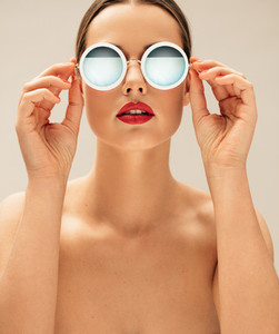 Shirtless female model wearing sunglasses